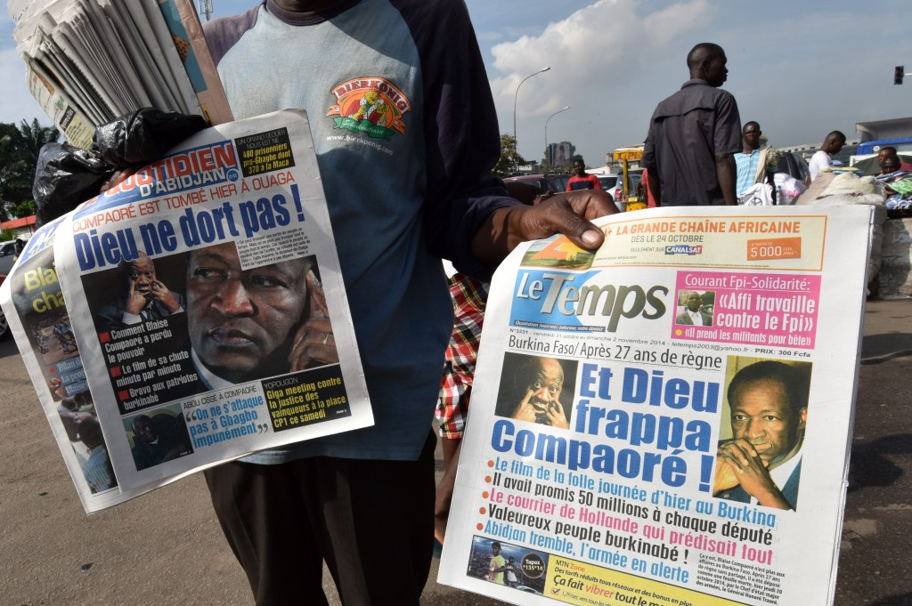 A man in Abidjan, Ivory Coast, sells daily newspapers leading with stories about the recent events in Burkina Faso on Oct. 31. Photo by Sia Kambou/AFP/Getty Images