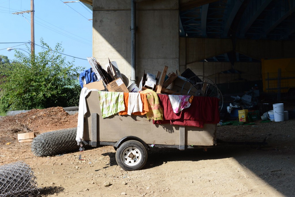 A wagon filled with garden tools and materials sits under the Route 2 viaduct. Photo by Ariel Min/PBS NewsHour