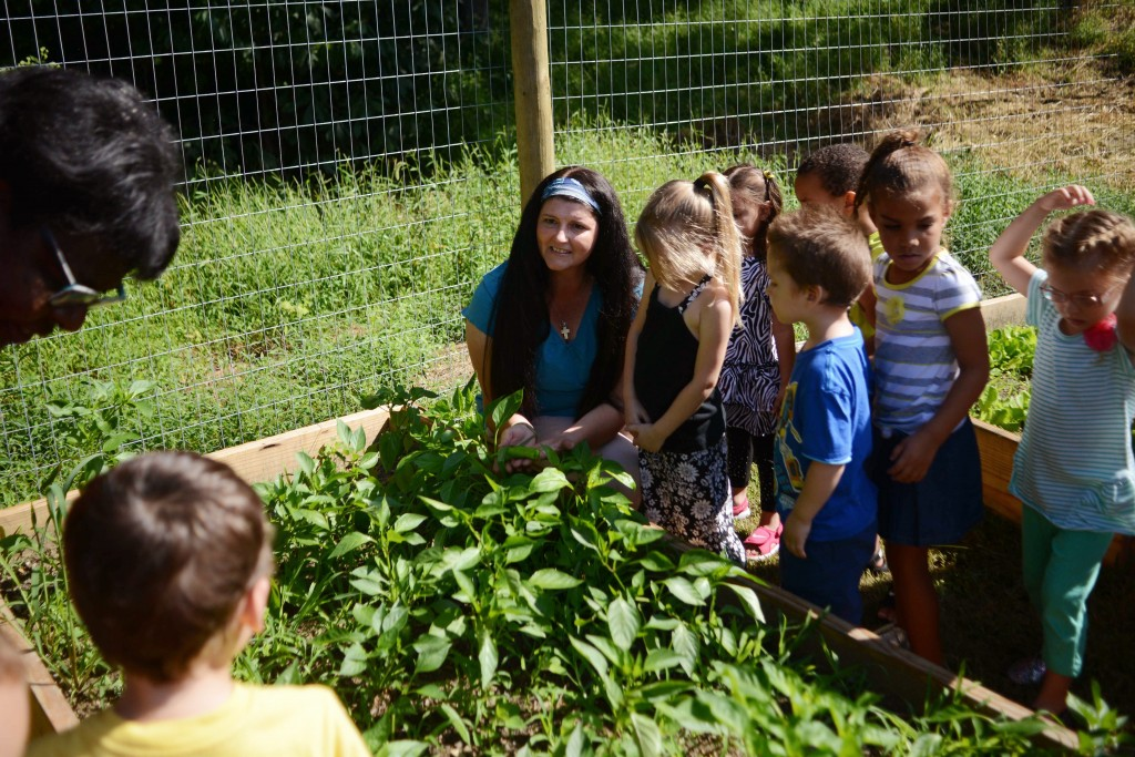 Kate Marshall shows the kids at Northern Panhandle Head Start what they can grow in their new community garden. Photo by Ariel Min/PBS NewsHour