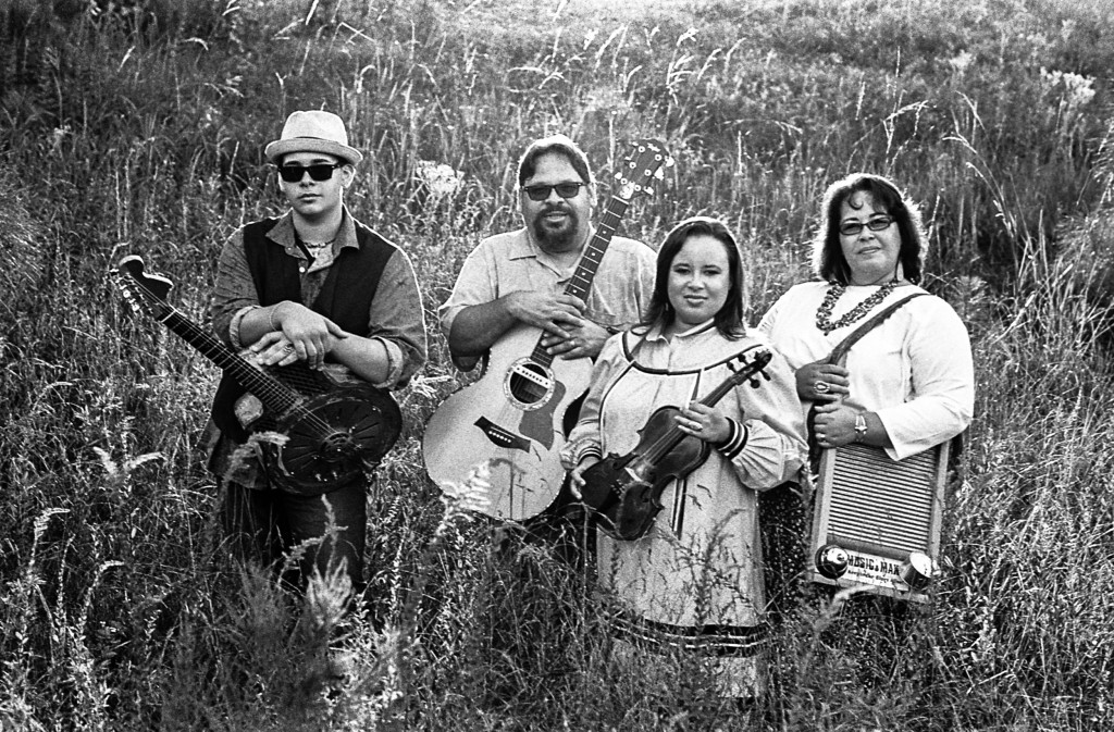 "Lakota John, Layla, Papa John & Tonya Locklear, Lumberton, North Carolina, 2013. ""John Lakota Locklear, born in 1997, grew up listening to his dad's music collection. At 7 years old, he picked up the harmonica and at 9, his first guitar. Intrigued by the sound of the slide guitar, by 10 he had bought himself a glass slide, placed it on his pinky finger and has been sliding ever since."" Photo courtesy Tim and Denise Duffy"