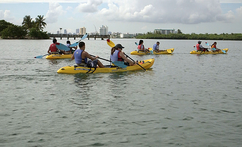 Daniel Hernandez (foreground, left), 16, a sophomore with autism at American Senior High School, teaches April Brown (foreground, right) the basics of kayaking in Miami's Biscayne Bay.  Photo by Mike Fritz/PBS NewsHour