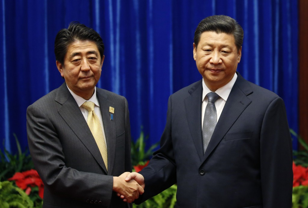 China's President Xi Jinping (right) shakes hands with Japan's Prime Minister Shinzo Abe, during their meeting at the Great Hall of the People, on the sidelines of the Asia Pacific Economic Cooperation (APEC) meetings, on Nov. 10 in Beijing, China. Photo by Kim Kyung-Hoon-Pool/Getty Images