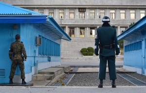South Korean soldiers stand guard as a North Korean soldier is seen at the truce village of Panmunjom in the Demilitarized Zone dividing the two Koreas on Nov. 12, 2014. File photo by Jung Yeon-Je/Getty Images