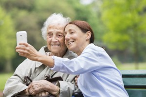 Caregiver and senior woman taking selfie portrait with smart phone. Photo by FredFroese/Getty Images