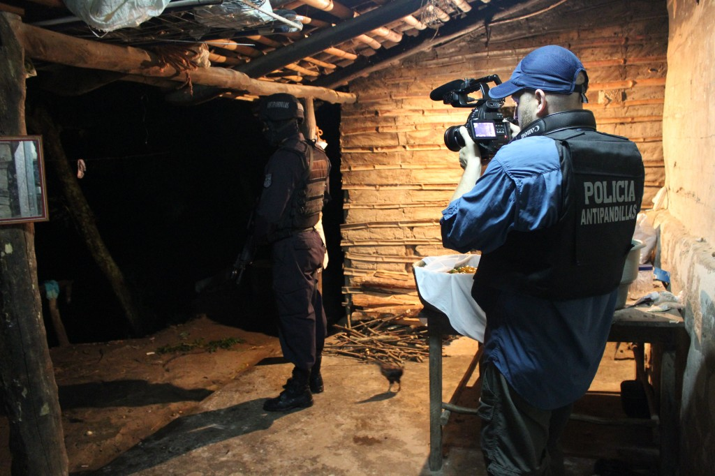 NewsHour Producer Brian Epstein filming during a police raid on suspected gang members in El Salvador. Credit: NewsHour
