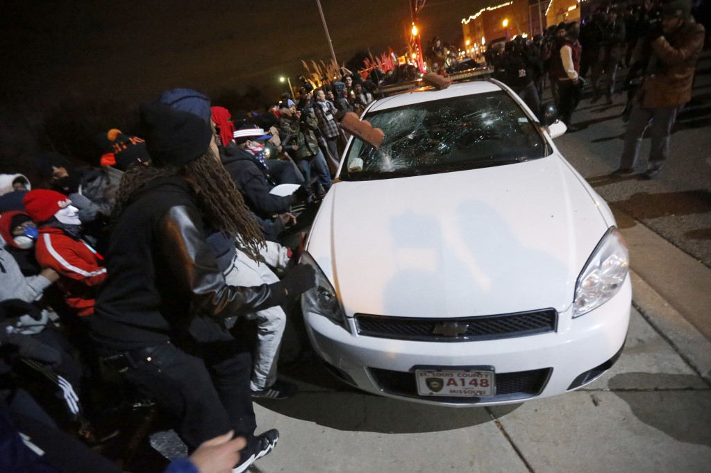 Protesters vandalize a car outside the Ferguson Police Department in Ferguson, Missouri. Photo by Jim Young / Reuters