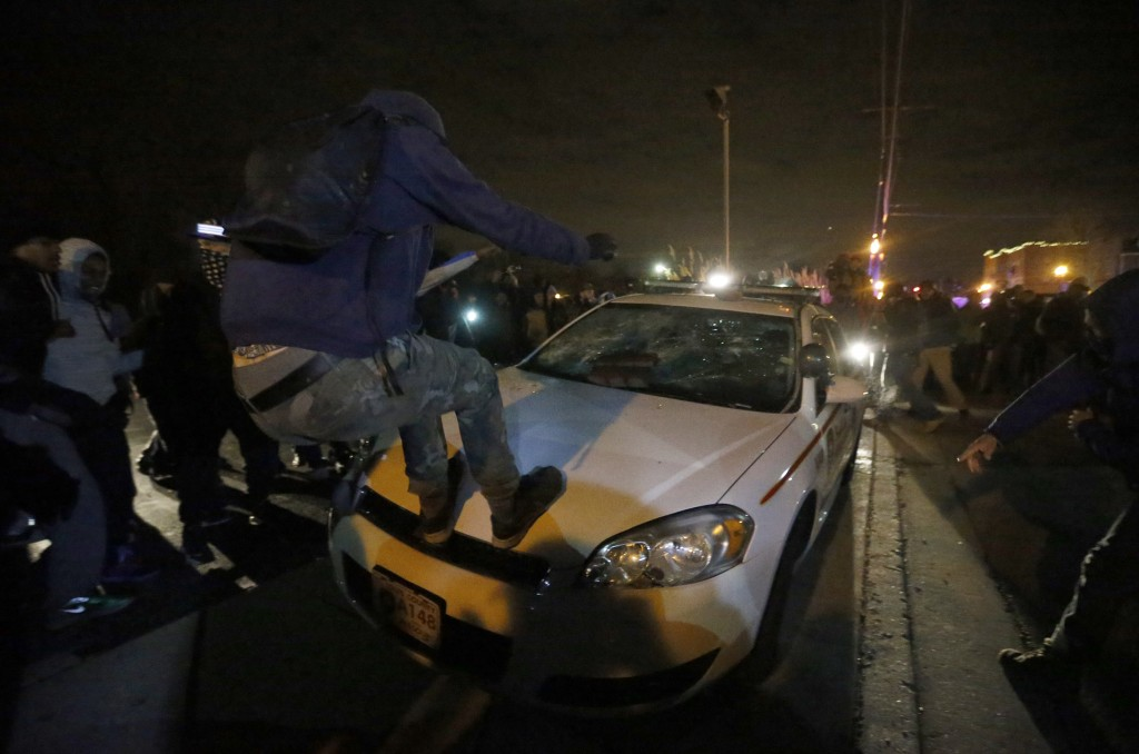 Protesters vandalize a car outside the Ferguson Police Department in Ferguson, Missouri, after a grand jury returned no indictment in the shooting of Michael Brown on November 24.   Photo by Jim Young / REUTERS