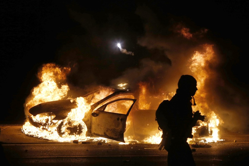 A police car burns on the street after a grand jury returned no indictment in the shooting of Michael Brown in Ferguson, Missouri. Photo by Jim Young / REUTERS