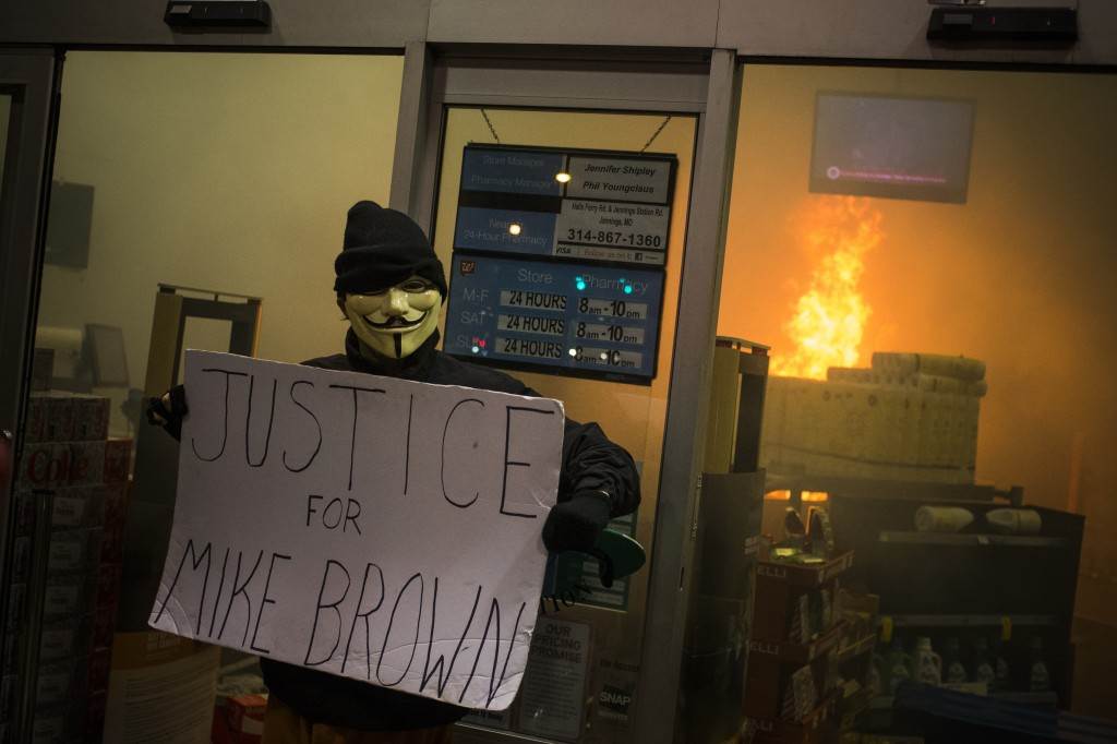 A protester holds a sign outside a burning Walgreens drug store after a grand jury returned no indictment in the shooting of Michael Brown in Ferguson, Missouri, November 24. Gunshots were heard and bottles were thrown as anger rippled through a crowd outside the Ferguson Police Department in suburban St. Louis after authorities on Monday announced that a grand jury voted not to indict a white officer in the August shooting death of an unarmed black teen.  Photo by Adrees Latif