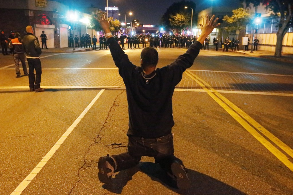 A man kneels in the road in front of a line of police during a demonstration in Los Angeles, California November 24, following the grand jury decision in the shooting of Michael Brown. Photo by Lucy Nicholson