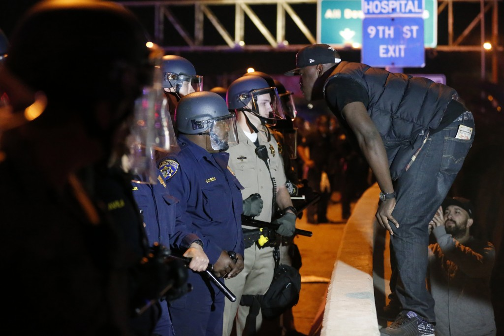 A protester faces off against a line of police on the 110 freeway during a demonstration in Los Angeles, California on November 24. Photo by Lucy Nicholson