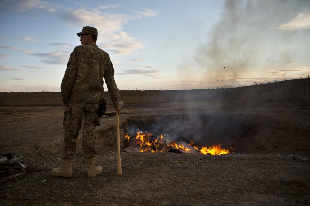 A U.S. Army soldier watches bottled water burn at Forward Operating Base Azzizulah in Maiwand District, Kandahar Province, Afghanistan, on Feb. 4, 2013. Photo by Andrew Burton/Reuters
