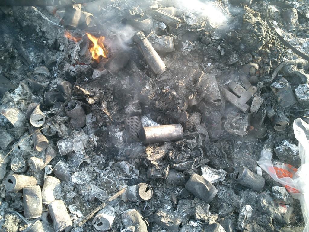 Burnt aerosol cans in an unidentified burn pit.