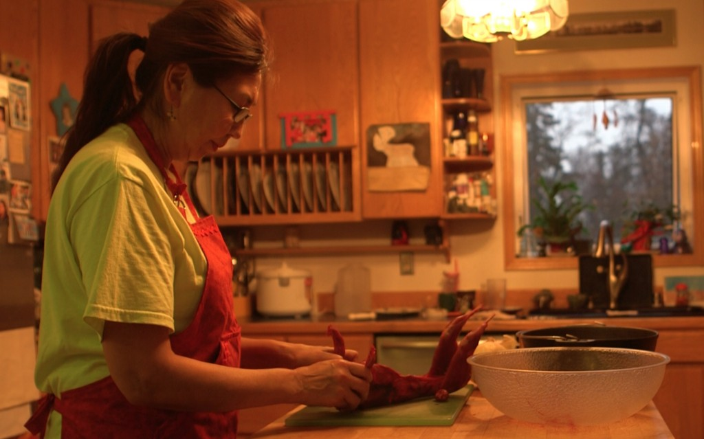 Ina Bouker who teaches students about Yup'ik traditions including subsistence hunting at schools in Dillingham, Alaska prepares rabbit freshly caught by her son John for the family's dinner. Photo by Mike Fritz/PBS NewsHour