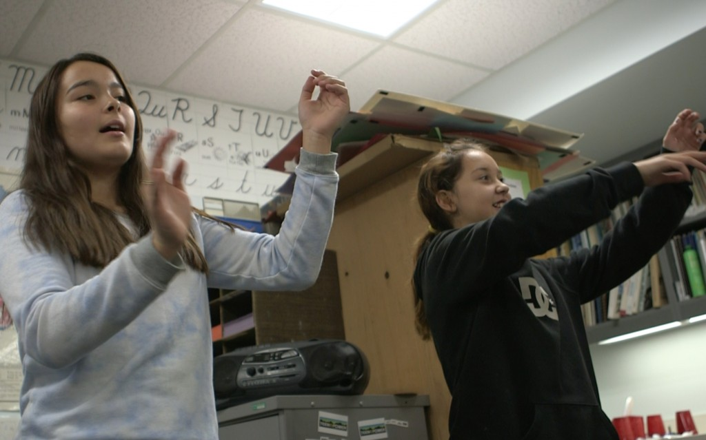 Theresa Williams (L) and Cate Gomez (R) practice a traditional Yup'ik dance at Dillingham High School in Dillingham, Alaska. Photo by Mike Fritz/PBS NewsHour