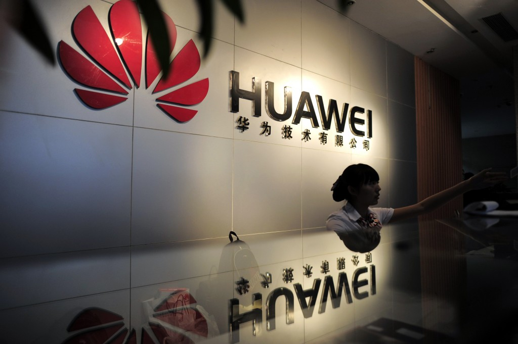 A receptionist sits behind the counter at the Huawei office in Wuhan, central China's Hubei province in 2012. Photo by STR...