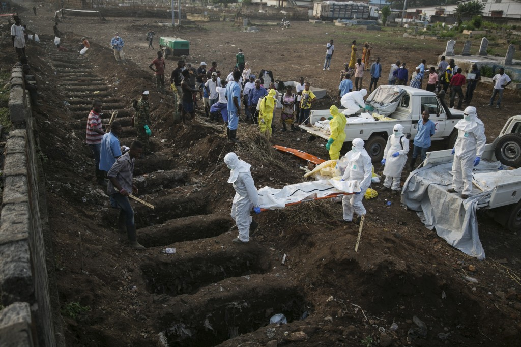 Health workers carry the body of an Ebola victim for burial at a cemetery in Freetown December 17, 2014. Photo by Baz Ratner/Reuters