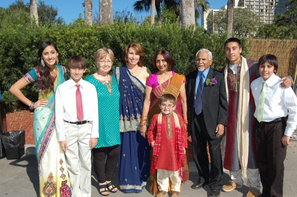 When Sheryl and Dharmesh Parbhoo married more than 20 years ago, their family united different religions and cultures. Here, left to right, Sheryl (center) stands with her daughter, Alyssa, twin son, Adam, her mother Jean Bryant, her youngest son, Chase, her mother-in-law, Sarla Parbhoo, her father-in-law, Baloo Parbhoo, her son, Nick, and her other twin son, WIlliam, during a family wedding in Orlando, Florida. Photo courtesy of Sheryl Parbhoo.