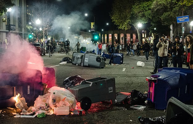Protesters look on as trash cans set on fire in the middle of downtown Berkeley smolder during Sunday night's protest. Photo by Benjamin Shenouda/Daily Californian