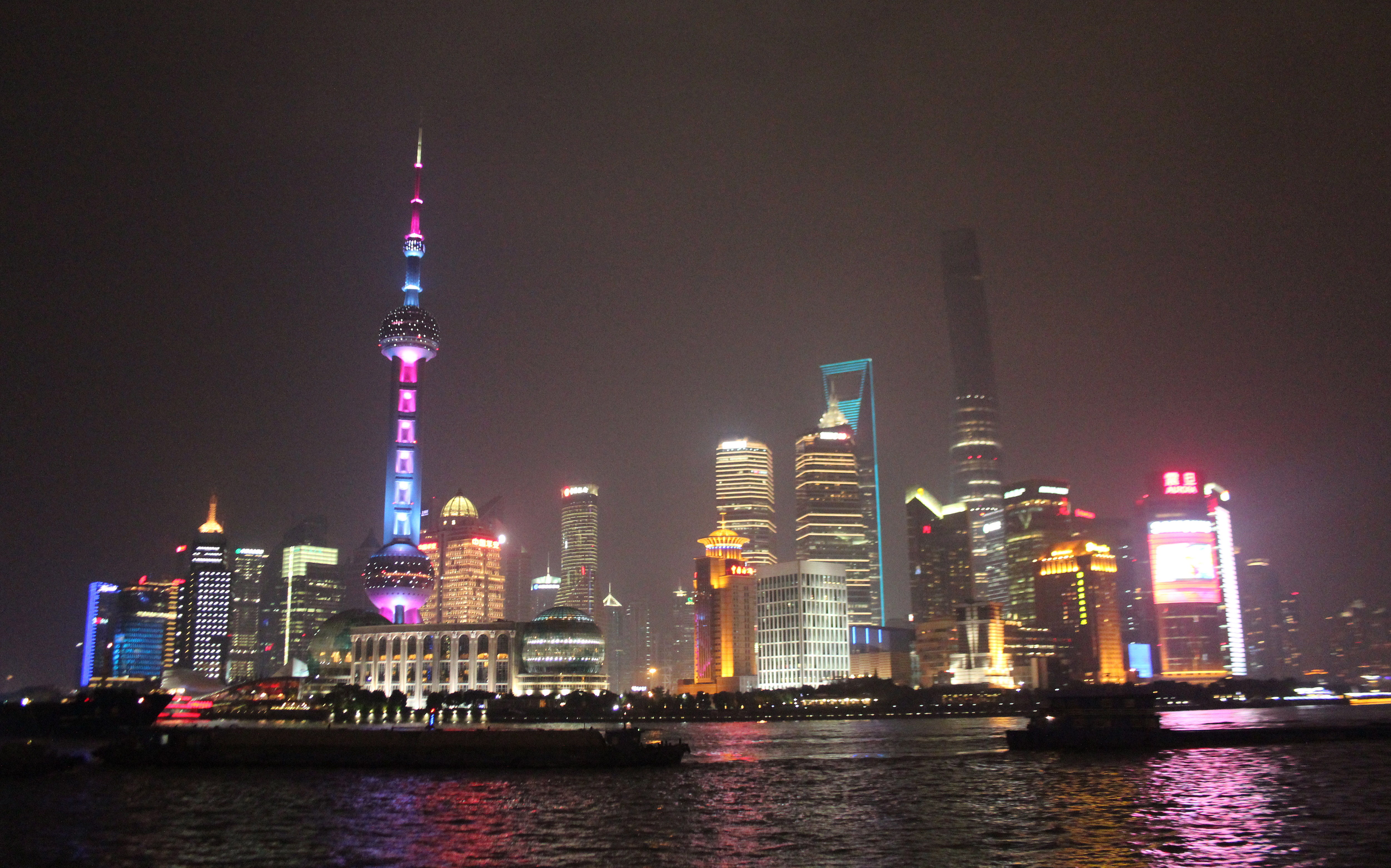 Shanghai's skyline, which features the Pearl television tower and a building shaped like a bottle opener, lights up in neon colors at night. Photo by Larisa Epatko/PBS NewsHour