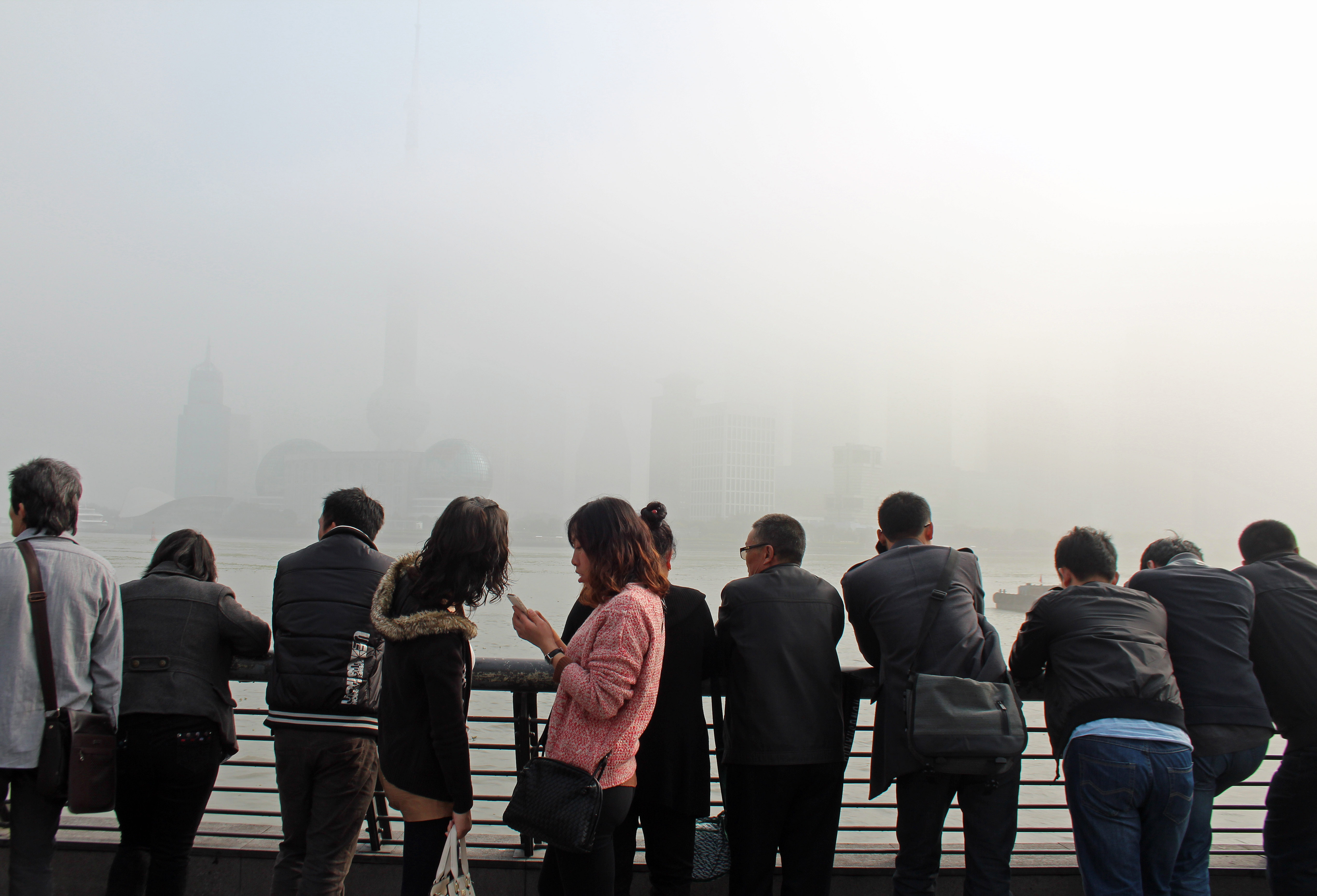 A nearly invisible skyline, from air pollution and fog, doesn't stop tourists from taking pictures in Shanghai. Photo by Larisa Epatko/PBS NewsHour