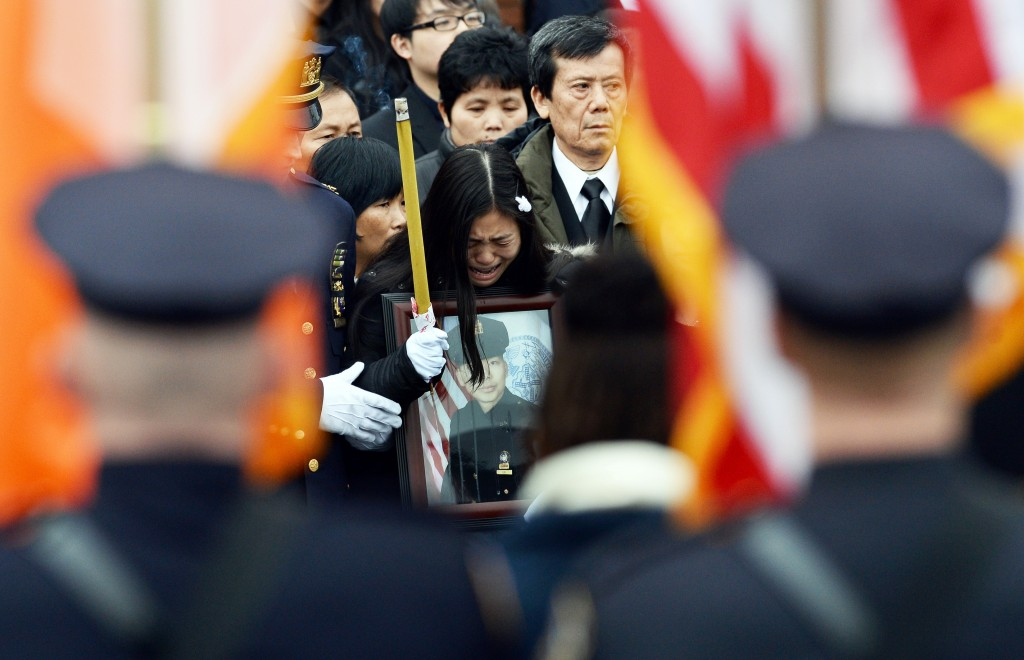 Pei Xia Chen (C) widow of New York Police Department (NYPD) officer Wenjian Liu cries holding a picture of her husband during a funeral in New York's borough of Brooklyn on January 4, 2015. A sea of blue uniformed officers crowded around a Brooklyn funeral home to honor Wenjian Liu, 32, shot in the head with partner Rafael Ramos, 40, on December 20, 2014 as the pair sat in their patrol car. The brutal double-slaying at the hands of a black gunman claiming to be avenging the deaths of African-Americans during confrontations with police shocked the nation's largest city. AFP PHOTO/JEWEL SAMAD        (Photo credit should read JEWEL SAMAD/AFP/Getty Images)
