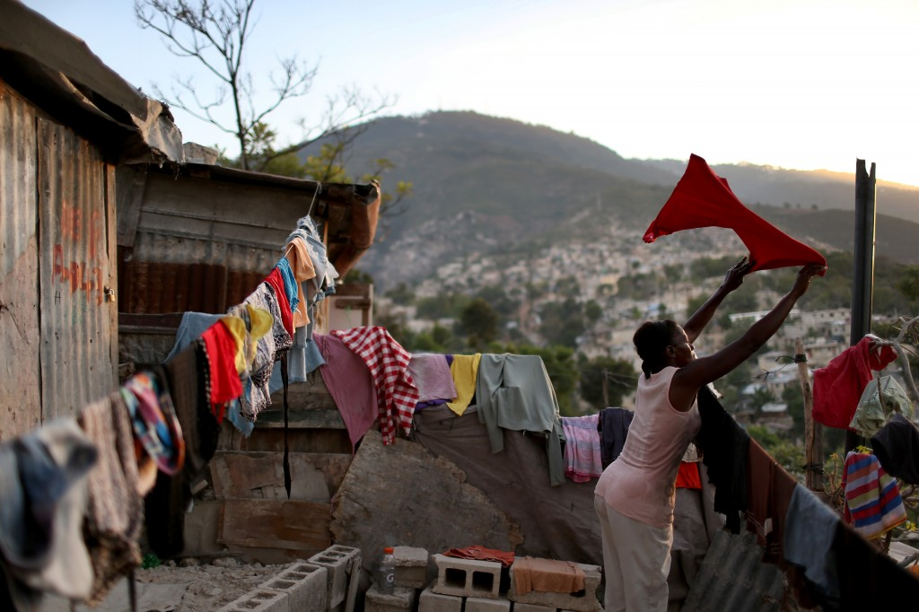 A woman hangs her laundry to dry in front of her home made out of tin and tarps that her family built over the land where their homes once stood before a magnitude 7.0 earthquake struck on Jan. 12, 2010, destroying their homes and killing as many as 316,000 people on in Port-au-Prince, Haiti. Five years later many of the tent camps and shantytowns that once sheltered some 1.5 million people now hold about 80,000 as the government tries to move them into permanent homes. Photo by Joe Raedle/Getty Images