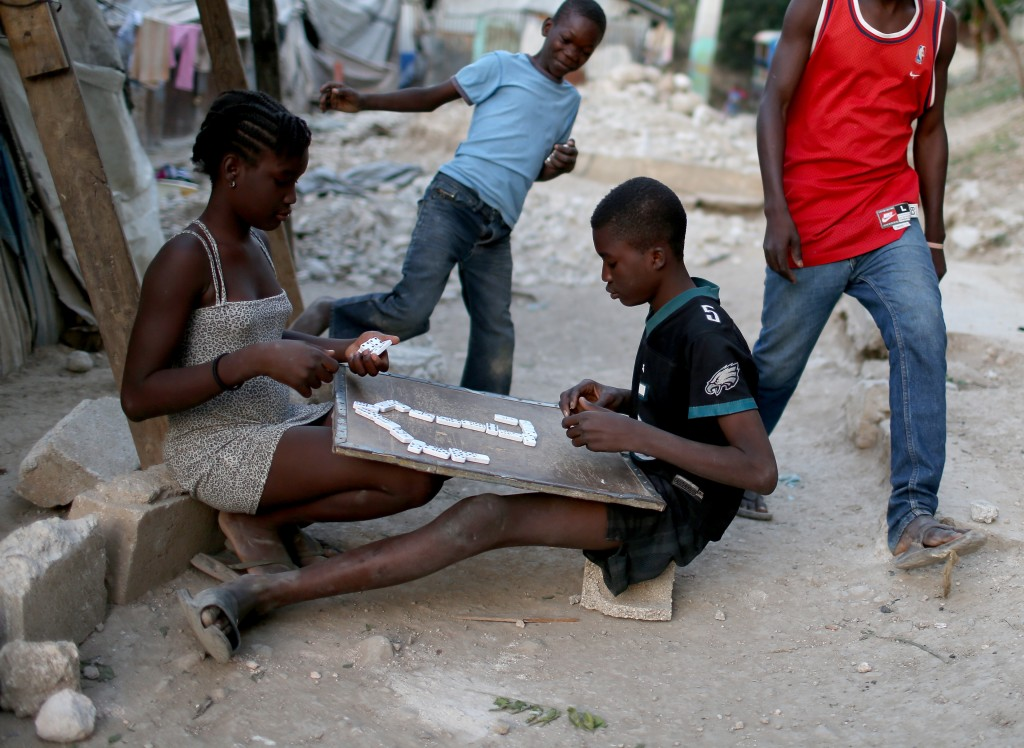 Children play a game of dominoes as they hang out together near the homes made out of tin and tarps that their families built over the land where their homes once stood before the Haiti earthquake. Photo by Joe Raedle/Getty Images