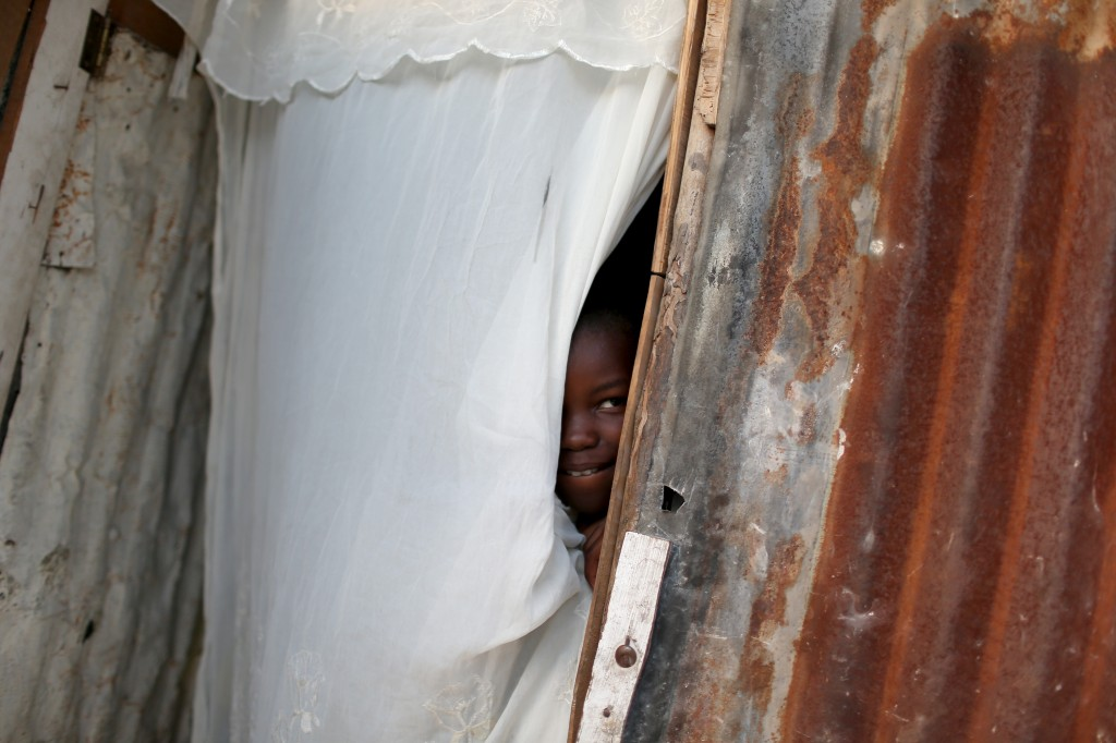 A young lady looks out from behind a cloth that serves as the front door to the home made out of tin and tarps that her family built over the land where their home once stood before a magnitude 7.0 earthquake struck Haiti five years ago. Photo by Joe Raedle/Getty Images