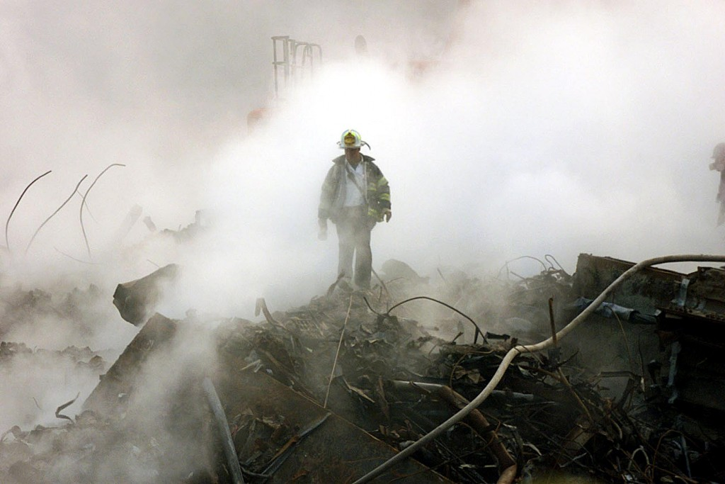 A fireman walks amongst the rubble and the smoldering wreckage of the World Trade Center 11 October 2001 in New York. An interfaith ceremony was held at ground zero in conjunction with the one month anniversary of the attacks, marked by the short prayer service and a moment of silence at 8:48am.