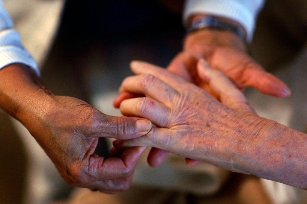 A United HomeCare Services home health aide massages the fingers of a patient during a home visit. Photo by Joe Raedle/Get...