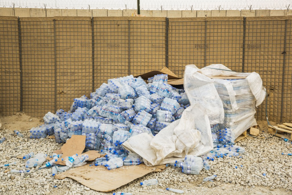 Cases of water bottles cascade out of shrink wrap in an area waiting to be cleared in order to shrink the massive Bagram Air Field in the Parwan province of Afghanistan on Jan. 2, 2015. Photo by Lucas Jackson/Reuters
