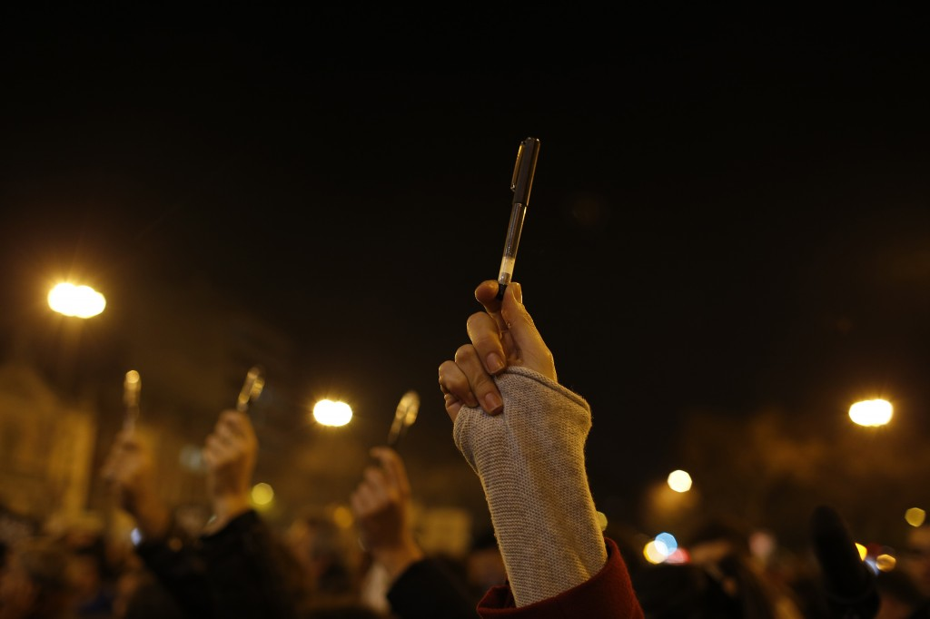 People participate in a vigil to pay tribute to the victims of a shooting, by gunmen at the offices of weekly newspaper Charlie Hebdo, in downtown Lisbon
