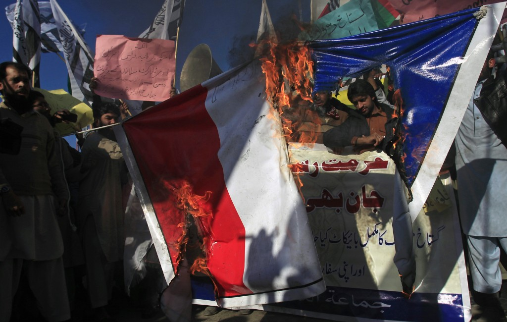 Supporters of the Jamaat-ud-Dawa Islamic organization burn a French flag during a protest against satirical French weekly newspaper Charlie Hebdo, which featured a cartoon of the Prophet Mohammad as the cover of its first edition since an attack by Islamist gunmen, in Peshawar January 16, 2015. REUTERS/Fayaz Aziz (PAKISTAN - Tags: MEDIA CIVIL UNREST POLITICS RELIGION) - RTR4LQEP