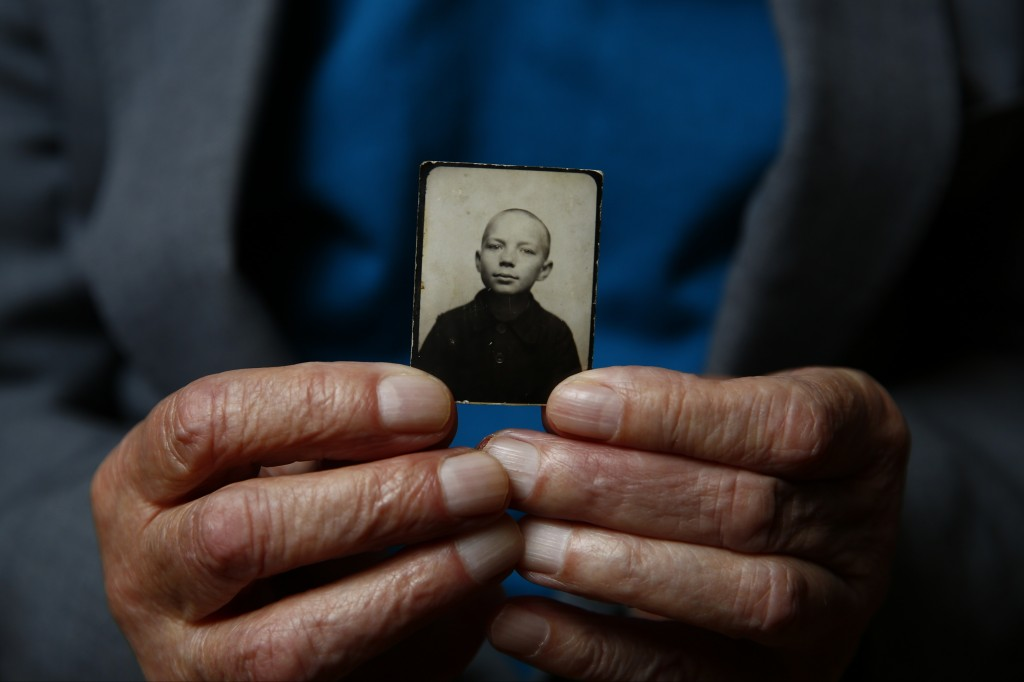 Auschwitz concentration camp survivor Stefan Sot holds a picture of himself taken during the war, in Warsaw