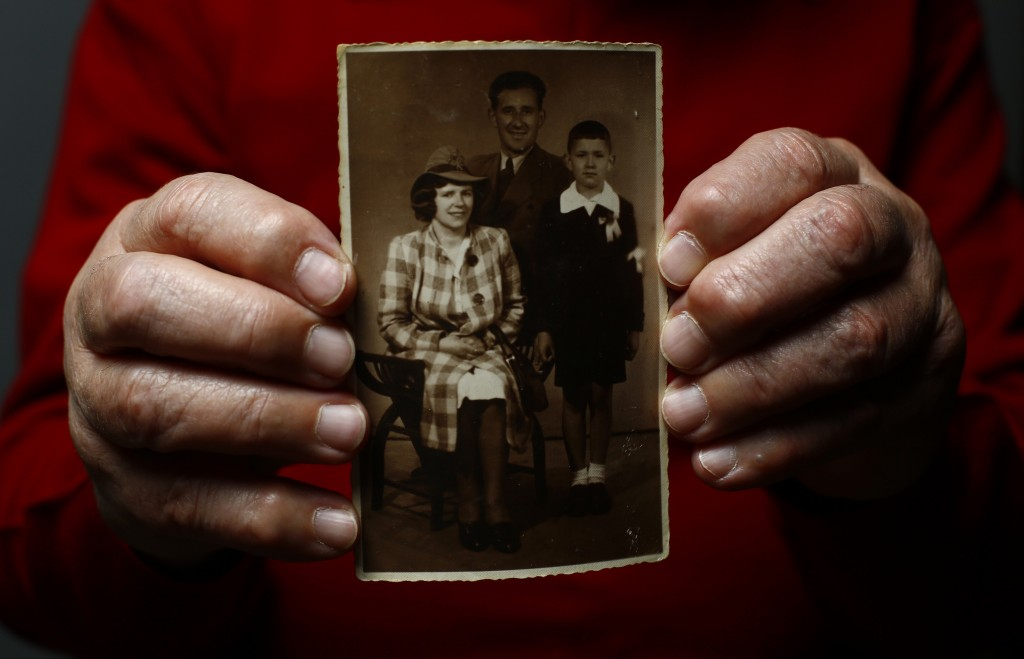 Auschwitz death camp survivor Bogdan Bartnikowski holds a family photograph as he poses for a portrait in Warsaw
