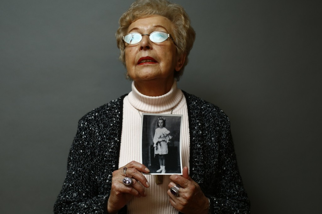 Auschwitz death camp survivor Janina Reklajtis holds a photo of herself taken during the war as she poses for a portrait in Warsaw
