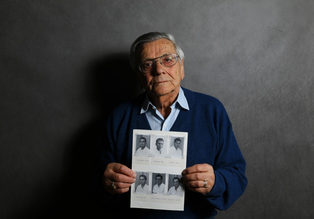 Auschwitz death camp survivor Imre Varsanyi holds up a photo of his fellow survivors during World War II as he poses for a portrait in Budapest