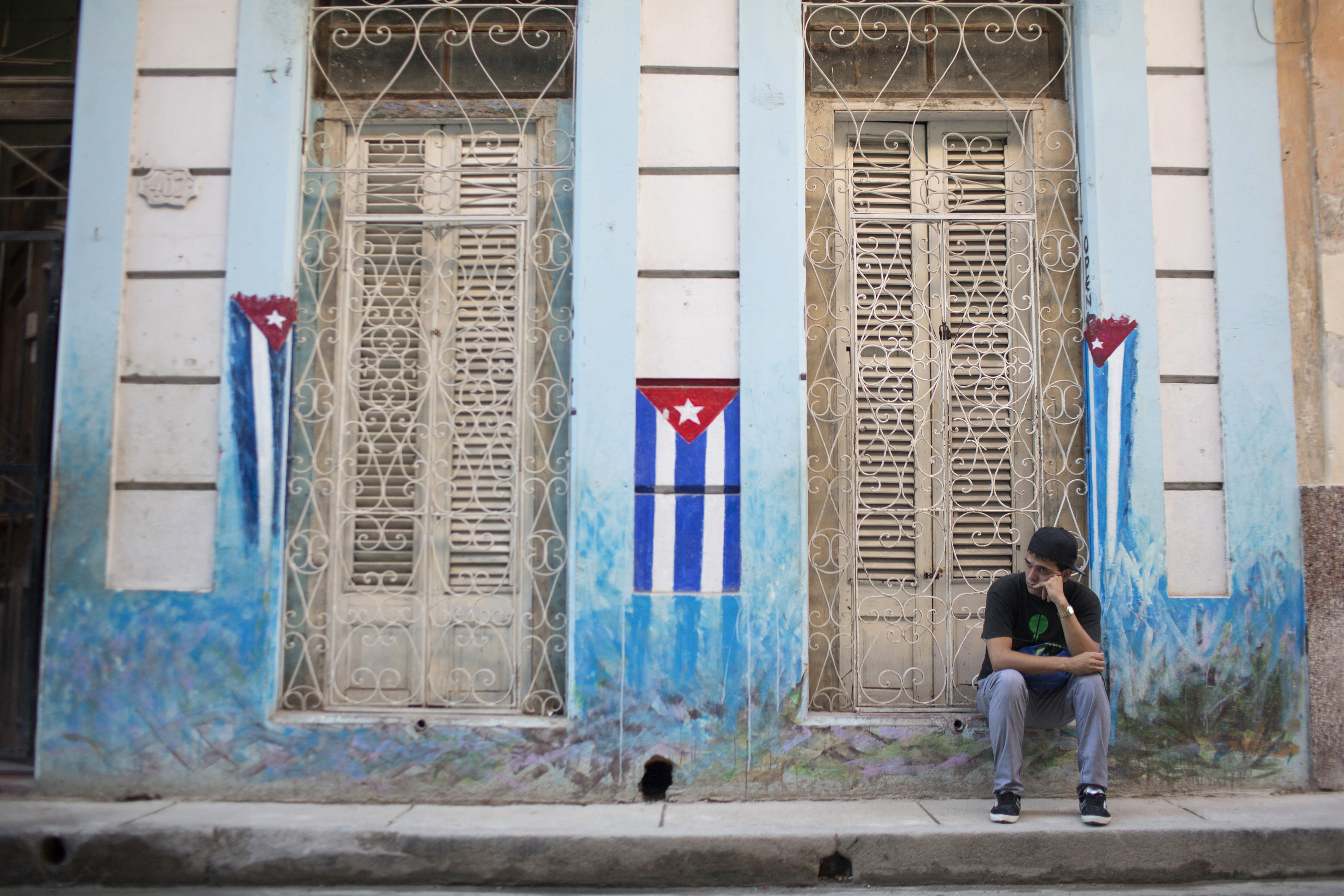 A man sits on the sidewalk next to Cuban National flags painted on the walls in downtown Havana, January 22, 2015. The United States and Cuba began historic discussions on restoring diplomatic relations on Thursday, aiming to reach agreement on the opening of embassies in each other's countries. REUTERS/Alexandre Meneghini (CUBA - Tags: SOCIETY POLITICS) - RTR4MI75