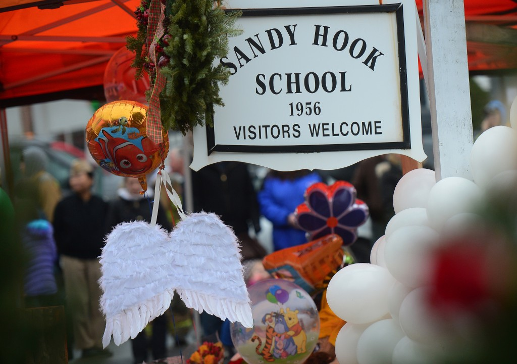 A pair of angel wings and balloons stand after being offered at a makeshift shrine to the victims of a elementary school shooting in Newtown, Connecticut, December 16, 2012.  A young gunman slaughtered 20 small children and six teachers on December 14,2012 after walking into a school in an idyllic Connecticut town wielding at least two sophisticated firearms. AFP PHOTO/Emmanuel DUNAND (Photo credit should read EMMANUEL DUNAND/AFP/Getty Images)
