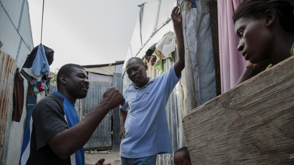 Jackson Doliscar of FRAKKA, left, speaks with camp residents. Photo by Ed Kashi/American Jewish World Service
