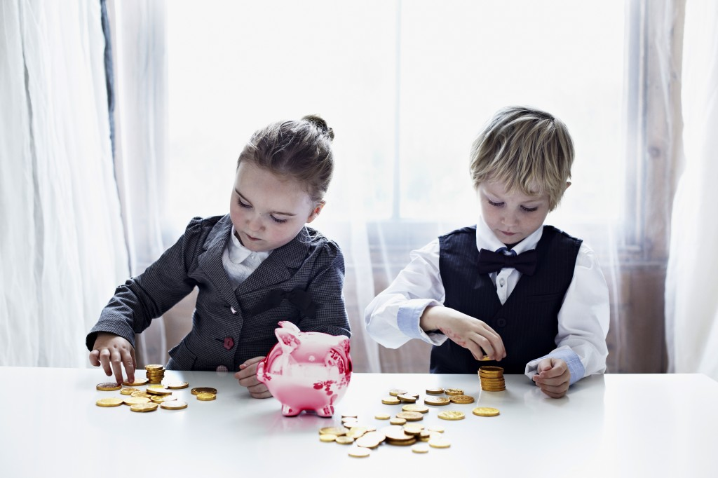 Children in suits counting gold coins. Kids dressed in suits playing with coins and a shiny piggy bank. Investing, investments, money. Cultura/Liam Norris via Getty Images