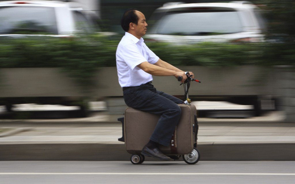 He Liang rides the suitcase vehicle that he spent 10 years perfecting along a street in Changsha, Hunan province. The tiny car can go as fast as 12 miles per hour and as far as 37 miles on a single battery charge, Chinese media reported. Photo by Reuters/China Daily.