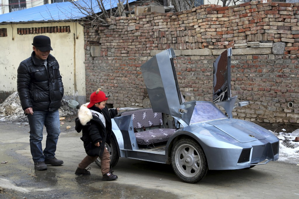 "Guo, left, a farmer in his 50s, looks on as his grandson gets on a scaled replica of a Lamborghini made by Guo, on a street in Zhengzhou, Henan province in China. Guo spent six months and about 5,000 yuan, or $821, to make the 2-meter-long, 1 meter-wide ""Lamborghini"" as a toy for his grandson. Guo built the replica out of scrap metal and electric bicycle parts. He installed five sets of batteries, enabling the toy car to travel nearly 40 miles when fully charged, Chinese media reported. Photo by Reuters/China Daily."