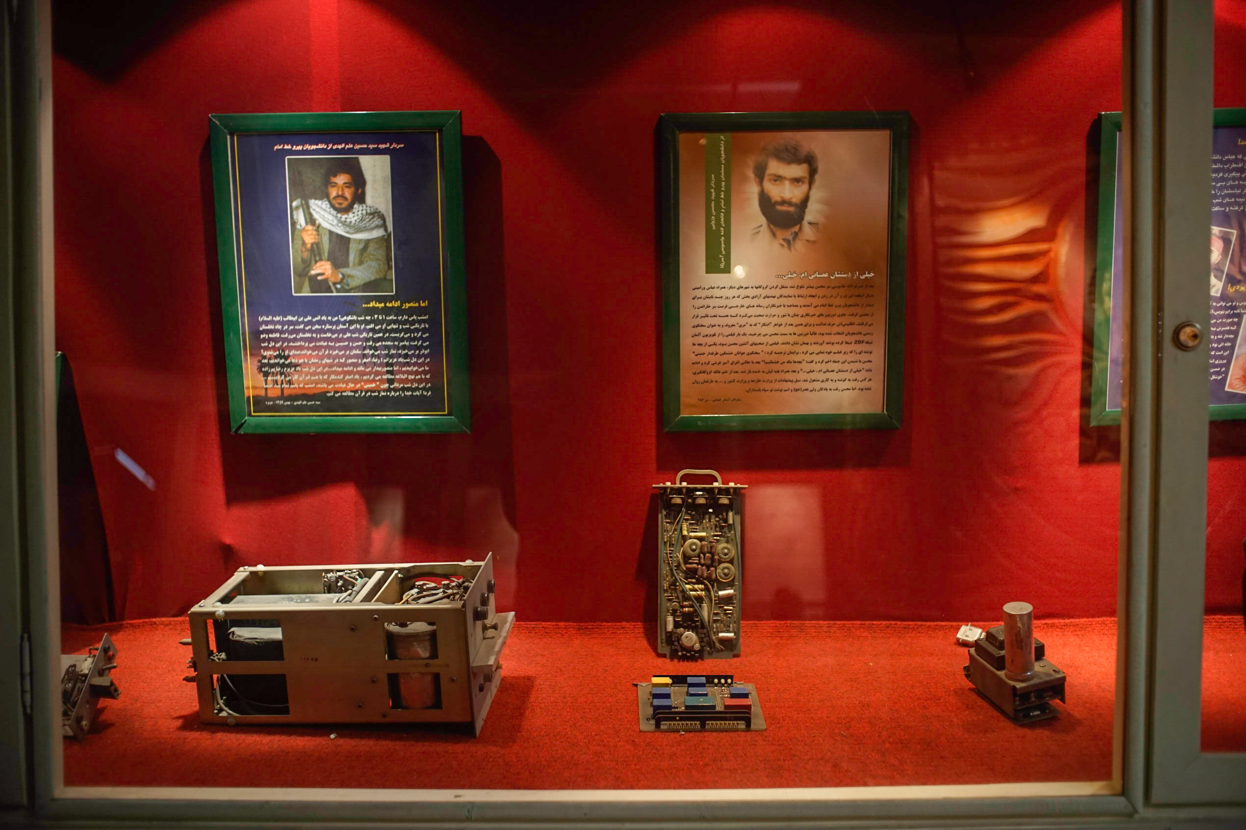 "More pieces of alleged surveillance equipment on display, along with posters celebrating certain  Iranian ""martyrs"" who, the posters claim, participated both in the takeover of the embassy and then later died fighting the Iraqis during the 1980's Iran-Iraq war."