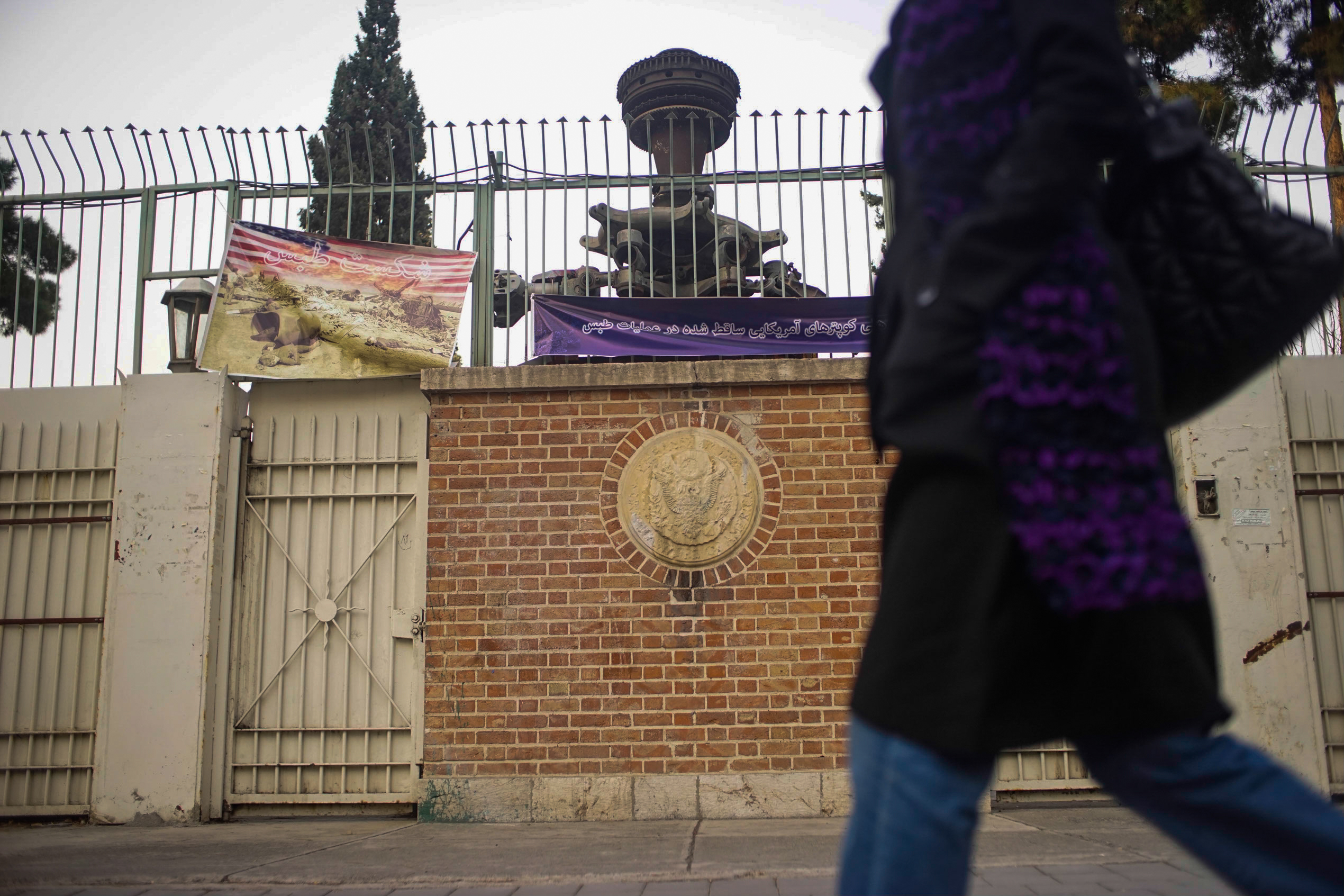 Entry gate of the former U.S. embassy in Tehran. The banner hanging upper left is allegedly a photo of the wreckage of the failed American rescue mission from 1980, where eight U.S. military members died when their aircraft were damaged in a sand and dust storm and crashed.  The Iranians claim the machine parts up behind the gate are from one of those U.S. aircraft.