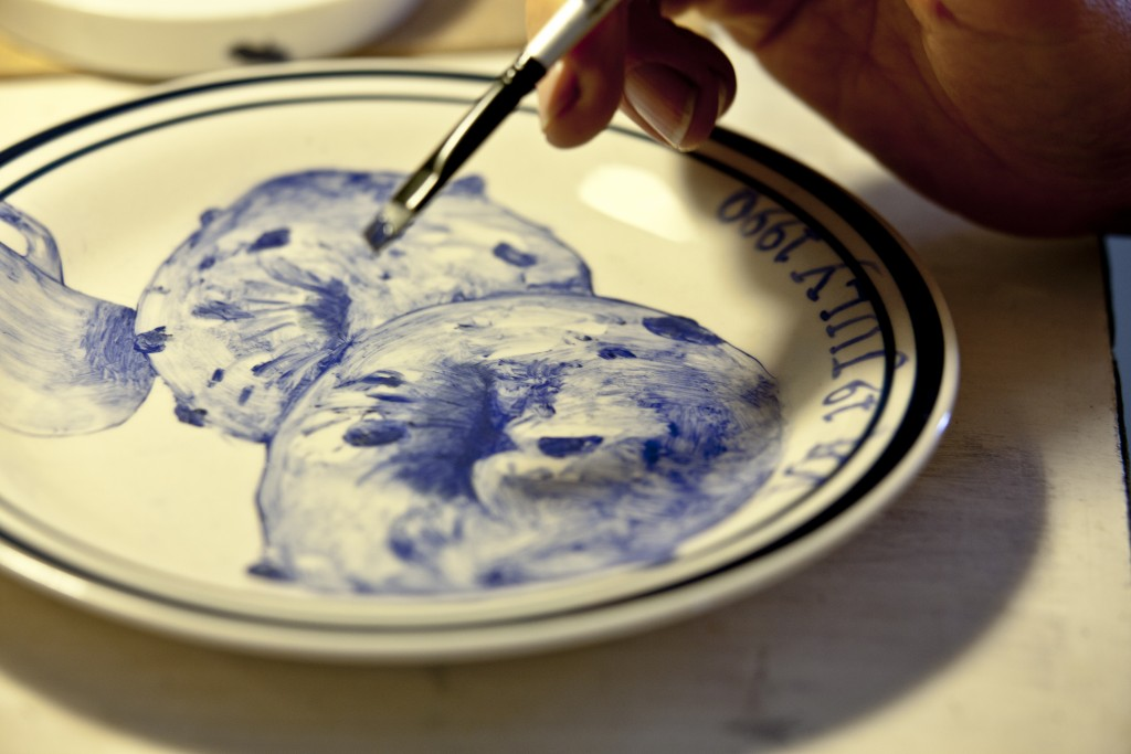 Julie Green applies cobalt blue mineral paint. Her technical advisor, Antoni Acock, kiln-fires every plate. Photo by Ha Lam, Whole Foods Market.