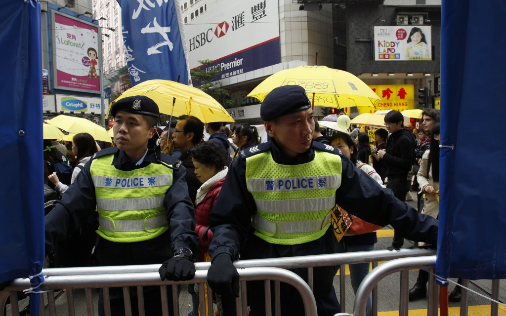 Policemen guard barriers during a demonstration in Hong Kong, February 1, 2015. Though protesters and police clashed in earlier protests, Sunday's march remained peaceful. Photo by Liau Chung-ren/Reuters