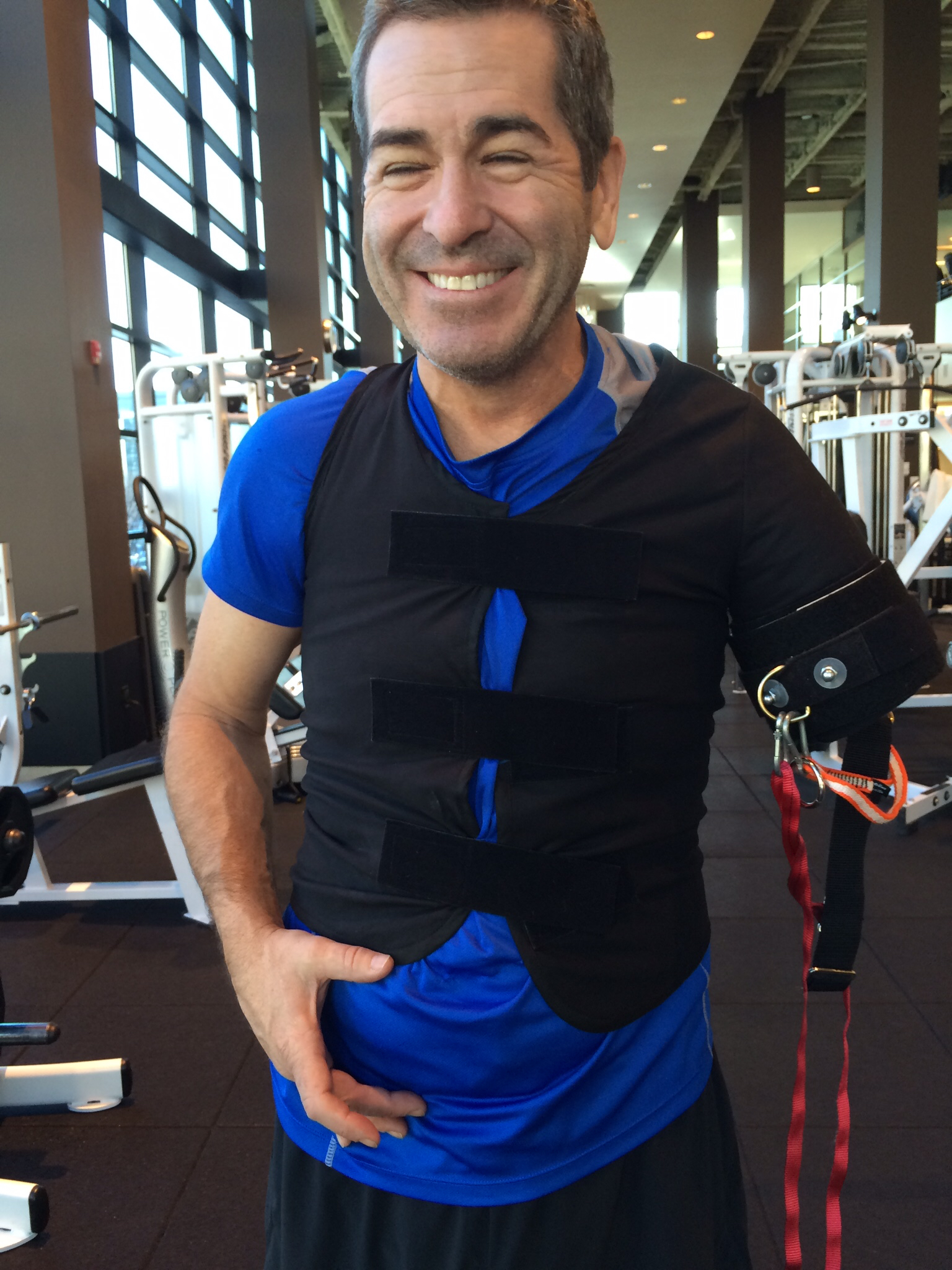"""Miles working out with a prototype """"Baker Rig"""" in development by a company called Adaptable Products. The device allows above elbow arm amputees to do weight training on the side of their body missing the limb. Photo by Suzi Tobias"""