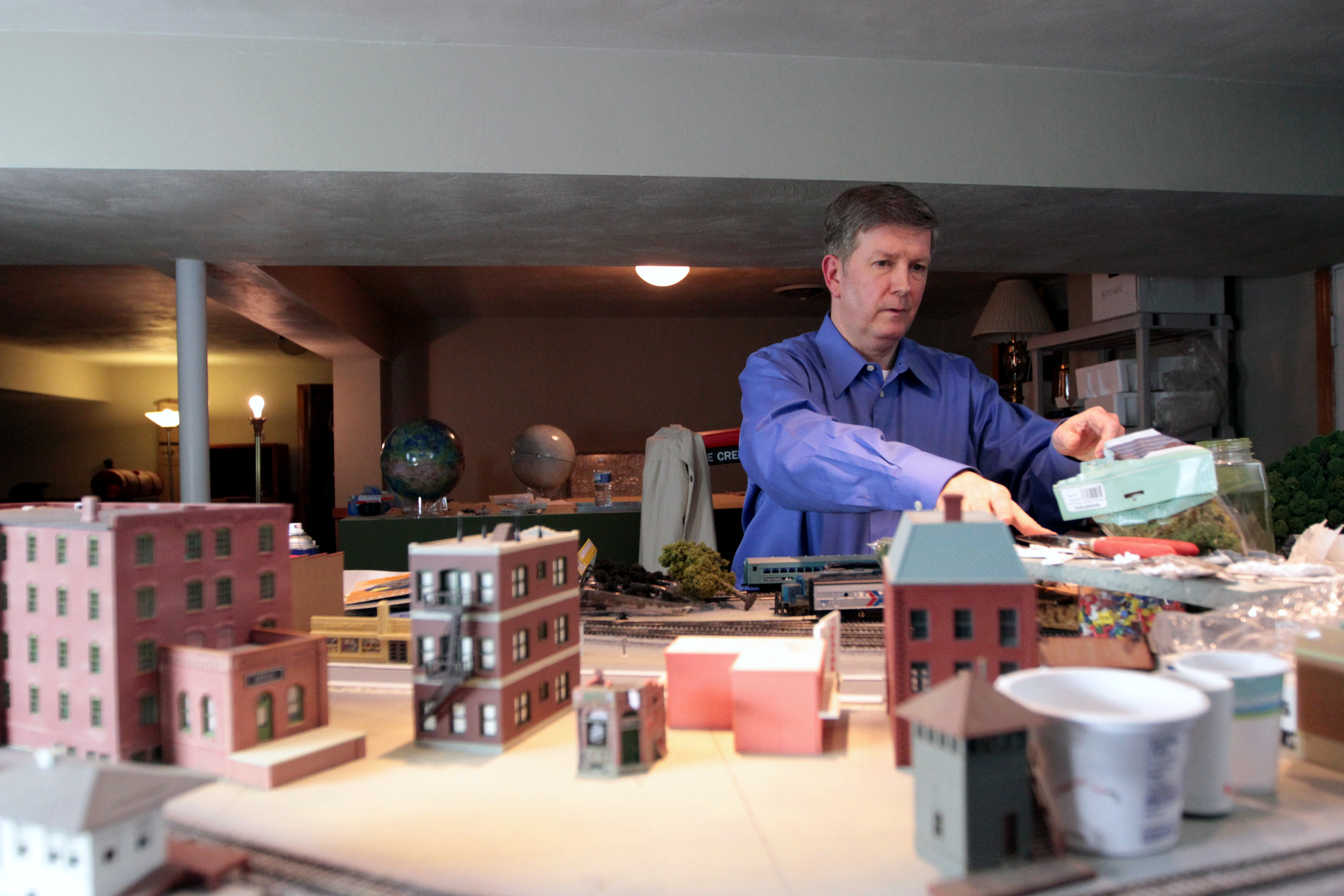 As a hobby, McDonnell works on his model railroad in the basement. Behind him are two globes of Venus and the moon, which he uses as reference maps for an online space exploration simulator. Photo by Eric Krupke/PBS NewsHour